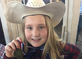 Ella Van De Kieft poses with her finalist medal at the Red Steagall Cowboy Gathering Children's Poe